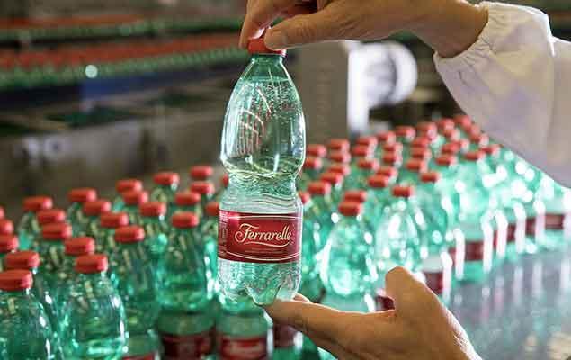Een lopende band met flesjes mineraalwater in een fabriek van Ferrarelle