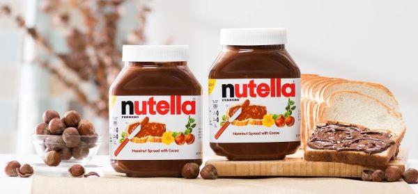 Twee potten Nutella, een boterham en hazelnoten