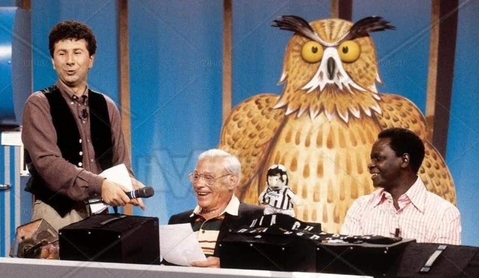 Een screenshot van het tv-programma Quelli che il Calcio met onder andere presentator fabio Fazio, Peter van Wood en op de achtergrond een grote uil